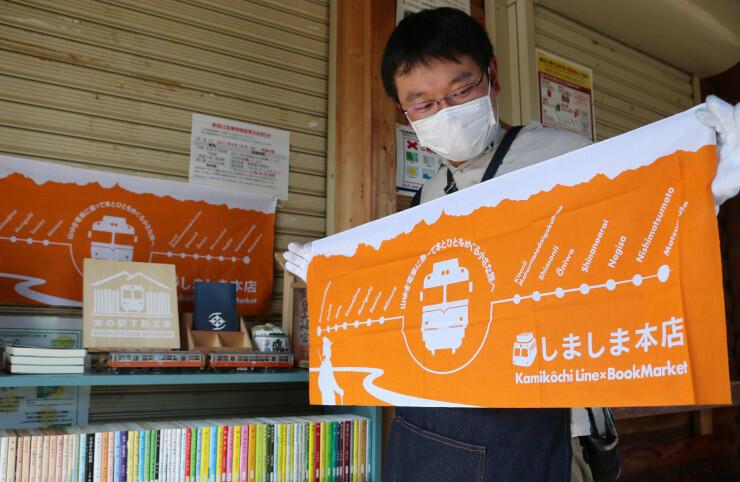収益の一部を上高地線復旧に活用しようと、新たに作ったオリジナルの手拭いをPRする太田さん