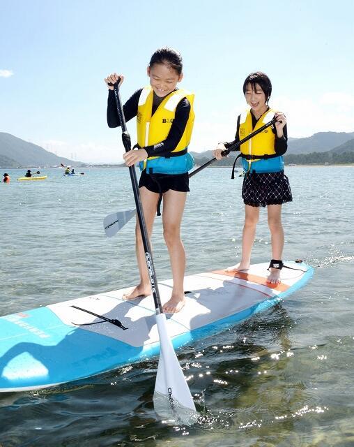 スタンドアップパドルを楽しむ参加者=8月28日、福井県高浜町事代の城山海水浴場