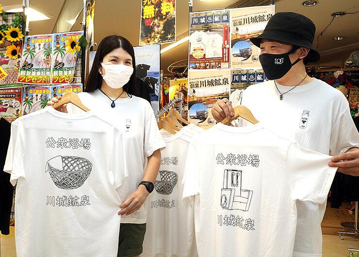 脱衣籠や牛乳瓶を描いたTシャツを手にする大久保さん(右)と松田さん