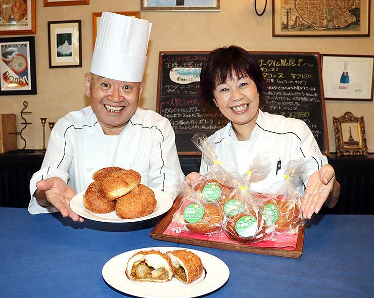 呉羽梨入りのカレーパンを手にする野口さん夫婦