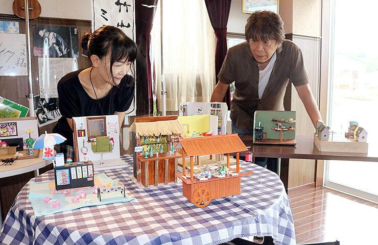 ミニチュアを眺める竹山さん(左)と矢後店長