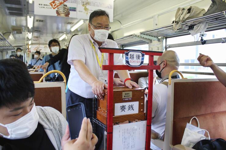 列車内にお目見えしたさい銭箱。鳥塚亮社長が自ら集めに回っている