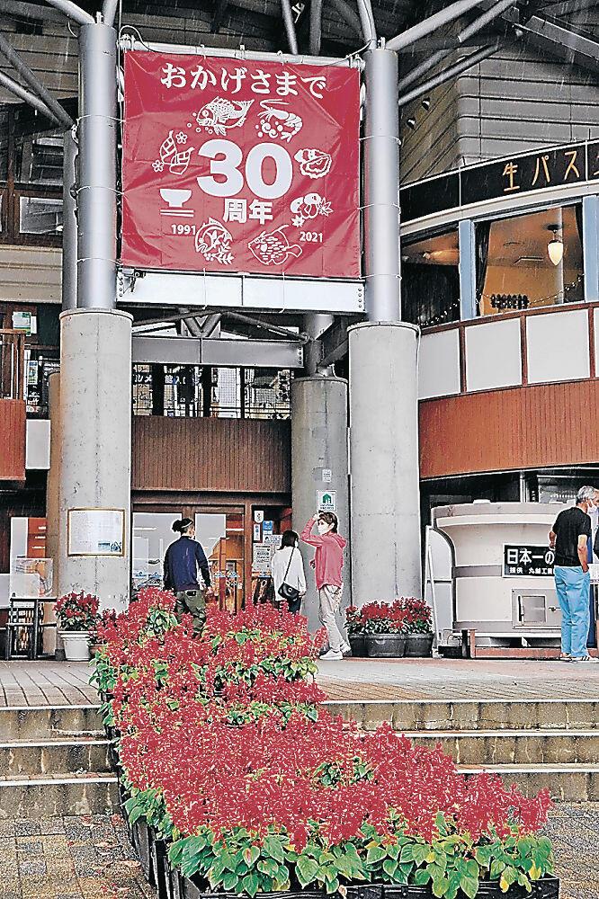 見頃を迎えたサルビアと30周年を祝う横断幕=七尾市の能登食祭市場