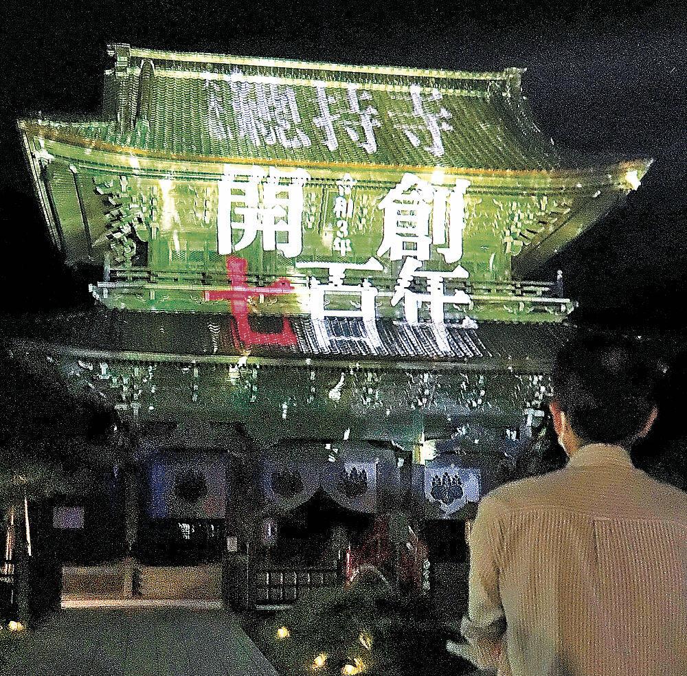 文字や鮮やかな映像が投影された山門=輪島市門前町の總持寺祖院