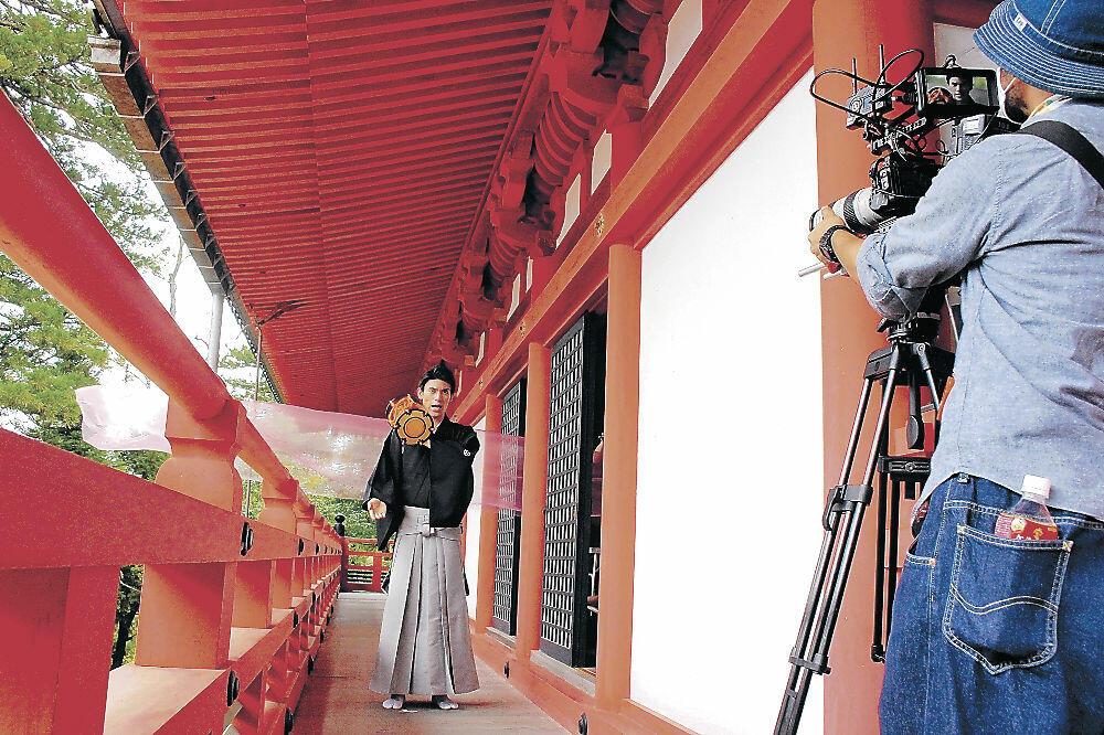 撮影に臨む出演者。サンコロナ小田が手掛けた極薄の織物(出演者後方)が用いられた=小松市の那谷寺