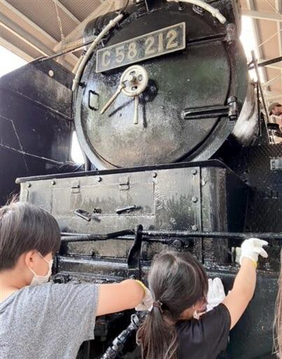 蒸気機関車を磨き上げる参加者=9月11日、福井県敦賀市の本町第3公園