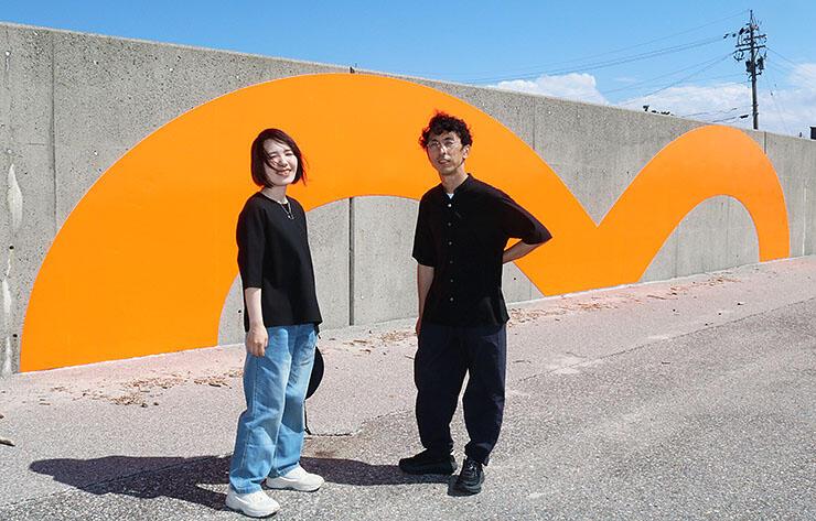 大きな「m」字型の作品の仕上がりを確認するため、現地を訪れた山下さん(左)と小林さん=生地海岸