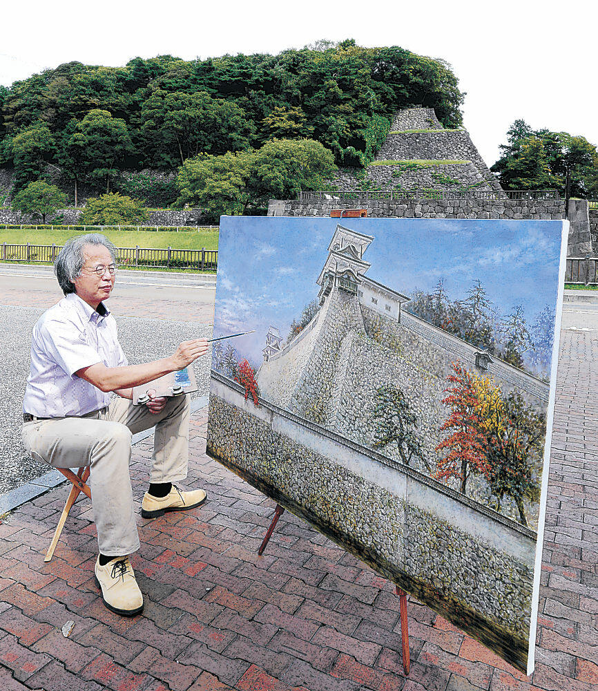 現地で作品に仕上げの筆を入れる末松さん。背景の石垣の頂部に辰巳櫓があった=金沢市広坂2丁目
