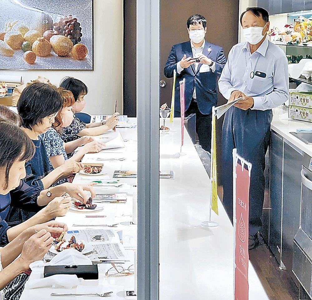 松浦さん(右)の説明を聞きながら黒蜜姫を味わう参加者=都内のフルーツ専門店