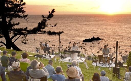 日本海に沈む夕日をバックに開かれたヒナタカコさんのライブ=福井県坂井市三国町の東尋坊