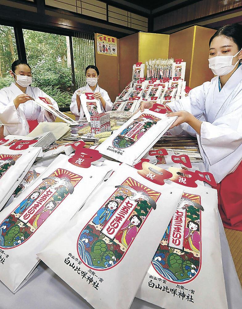 千歳飴などを袋詰めする舞女=白山市の白山比咩神社