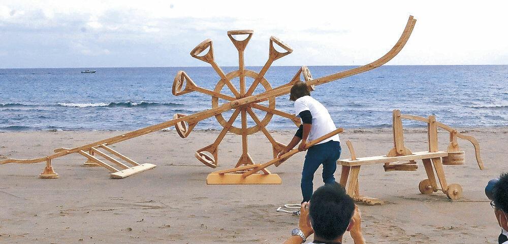 1日からの公開に向けて設置された砂浜にスタンプを押す作品=珠洲市の鉢ケ崎海岸