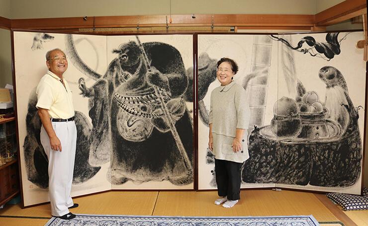 民谷さん(左)が保管する「老子出関の図」の右半分。右は妻のふみ子さん=富山市石坂の自宅