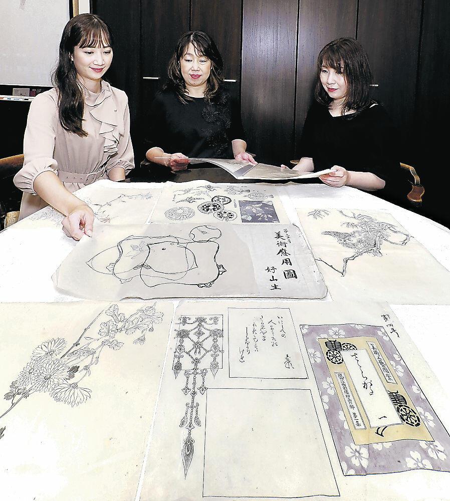 見つかった刺繍図案を確かめる横山さん(中央)=金沢市内