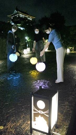 行灯がともる中、手持ちちょうちんで古城を散策する来場者=10月1日夜、福井県坂井市の丸岡城
