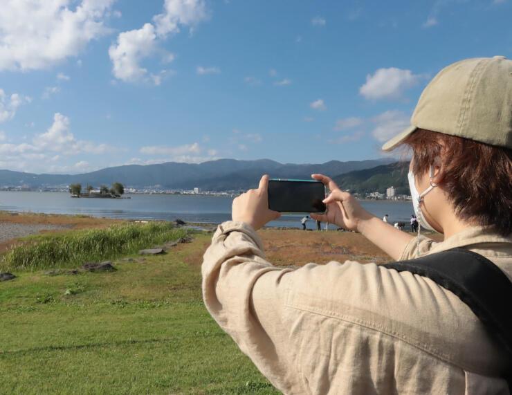 諏訪湖を撮影する観光客。こうした写真を投稿してもらう