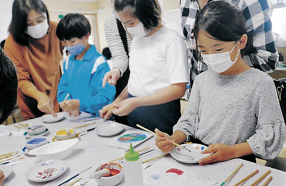 九谷焼の皿に絵付けを施す児童=加賀市打越町の九谷焼窯元「結窯」