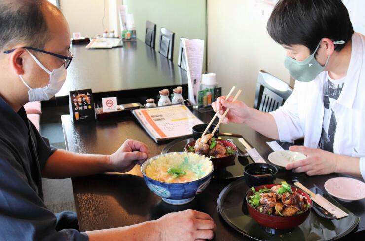 提供開始を前に、「鯉丼」(右と奥)の味を確かめる守屋さん(左)と中沢さん。「鯉天丼」(左)も試食した