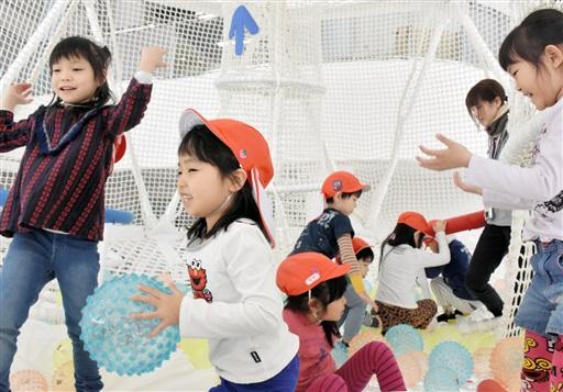 繭型ネット遊具の中でボール投げを楽しむ園児たち